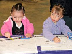 Two-year-old Krysta Connolly (left) and Sabin Delor, 4, color pictures for the Kick Butt Day coloring contest.