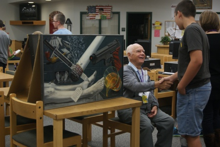 Artist Albert Ortiz (seated) greets a student at Desert Ridge Junior High School.