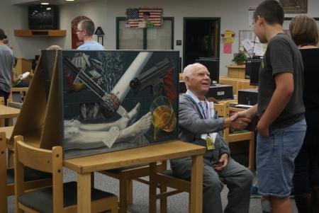Artist Albert Ortiz (seated) greets a student at Desert Ridge Junior High School.