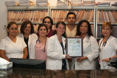 Gladys Cedillos of the Office of Tobacco and Chronic Disease Prevention (second from left) presents this award to the staff of Providence General Medicine & Pediatrics West Phoenix Office.