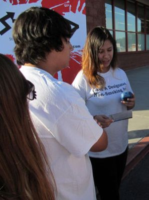 Photo: Courtesy Maricopa County Department of Public Health Dominique Arvizu, a senior at right, explains to her Ironwood High School classmate Abraham Smith, a sophomore, that he has passed a carbon monoxide breath test with flying colors. They were practicing with the device to help any smokers who stopped by their educational display outside a CVS store Nov. 20.